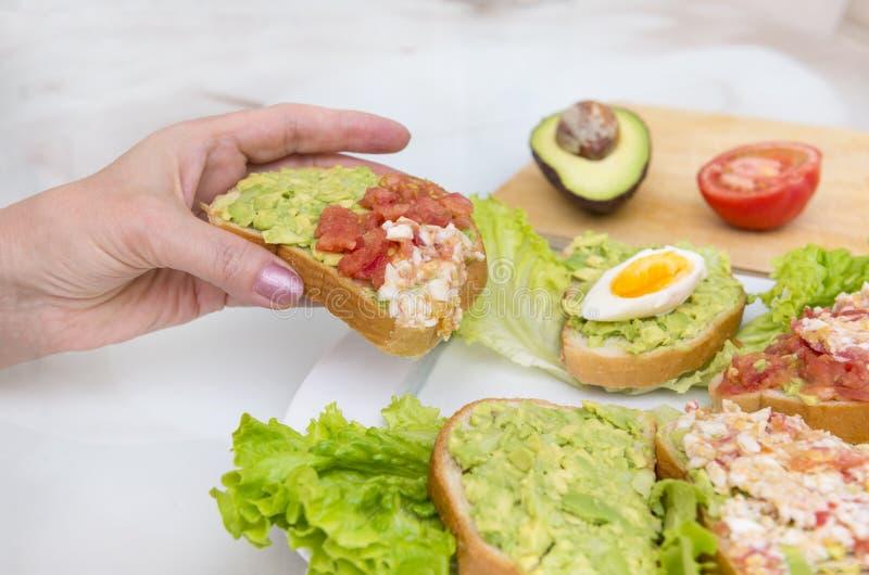 Passi la tenuta del panino con l'avocado, il pomodoro e l'uovo, spuntino con immagine stock