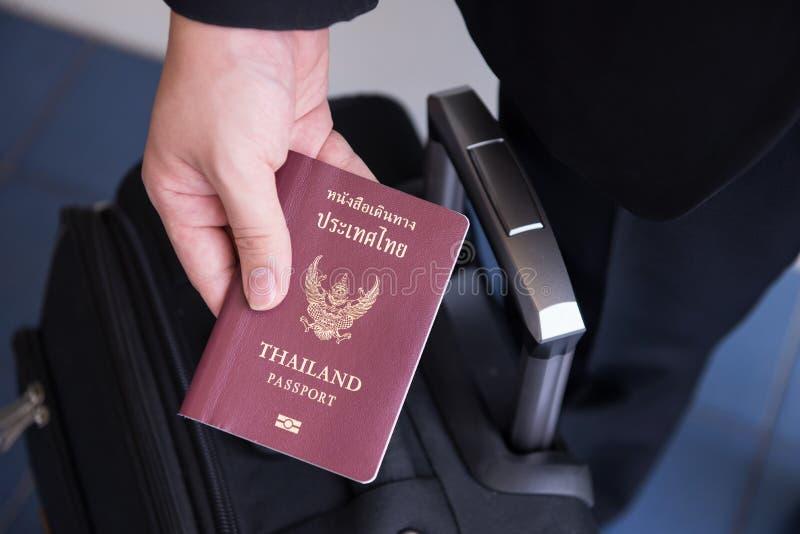 Passi la tenuta del passaporto tailandese, pronto a viaggiare immagini stock libere da diritti