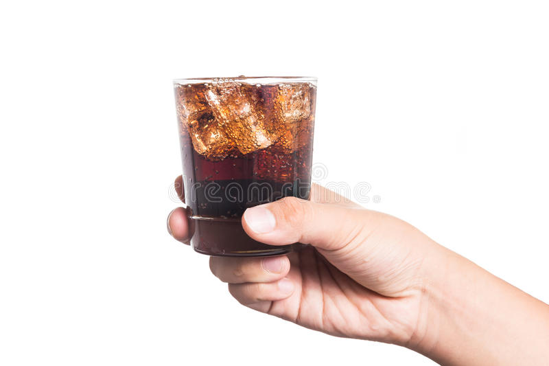 Passi la tenuta del vetro della bevanda fredda e gassate della cola riempita ghiaccio fotografia stock libera da diritti