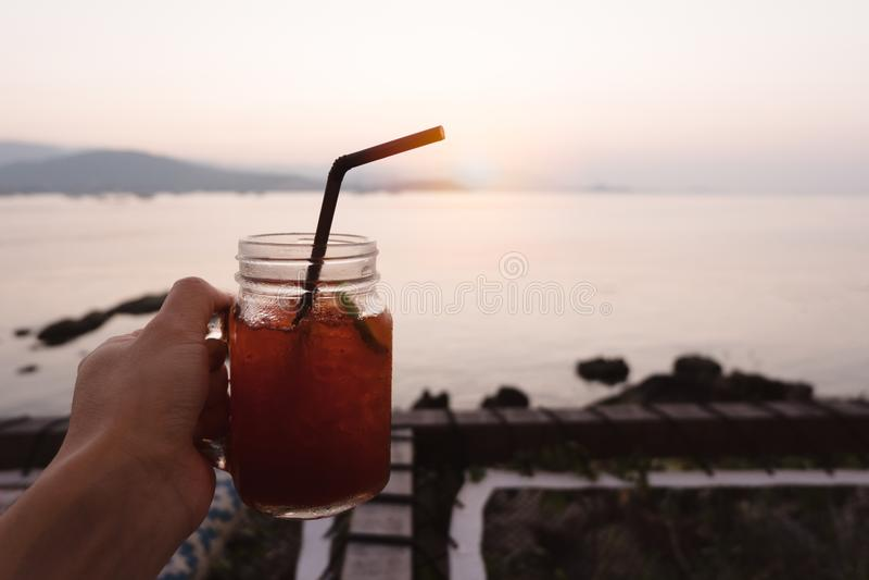 Passi la tenuta del vetro del tè di ghiaccio del limone sulla spiaggia tropicale del mare in sole immagini stock