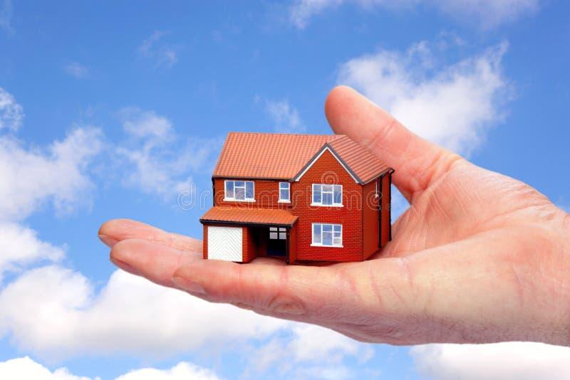 Passi la tenuta della casa di modello contro la priorità bassa del cielo. immagine stock libera da diritti