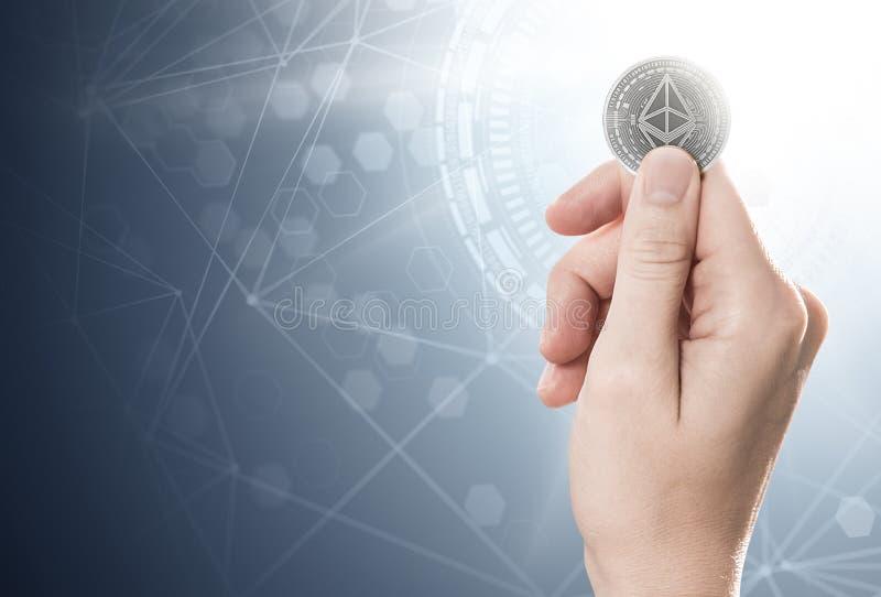 Passi la tenuta della moneta d'argento di Ethereum su un fondo luminoso con la rete del blockchain royalty illustrazione gratis