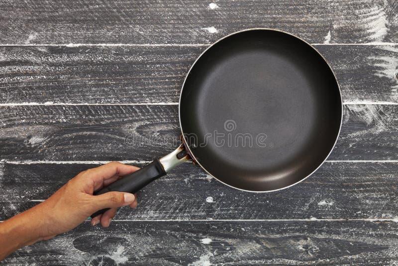 Passi la tenuta della padella vuota della cucina su fondo di legno nero fotografia stock
