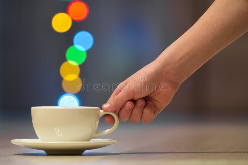 Passi la tenuta della tazza di caffè bianca con il vapore variopinto del bokeh immagine stock libera da diritti