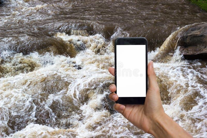 Passi la tenuta dello smartphone nero con lo schermo bianco per derisione su sulla s fotografia stock libera da diritti