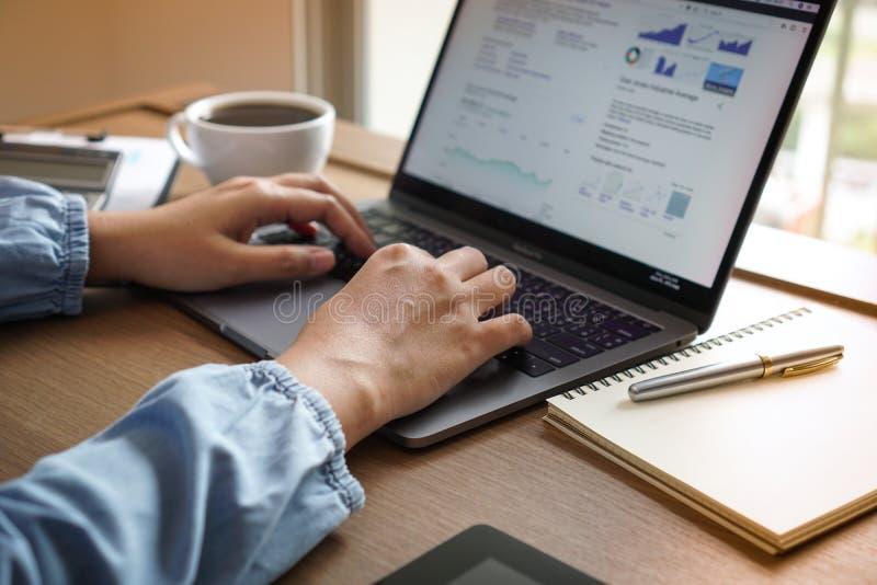 Passi le donne che fanno le finanze e calcoli sullo scrittorio circa costo ad uff fotografie stock
