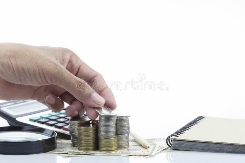 Passi le monete in dita e nelle pile di fila di monete con gli oggetti business su fondo bianco fotografie stock libere da diritti