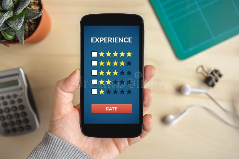 Passi lo Smart Phone della tenuta con il concetto di esperienza del cliente sull'SCR fotografie stock