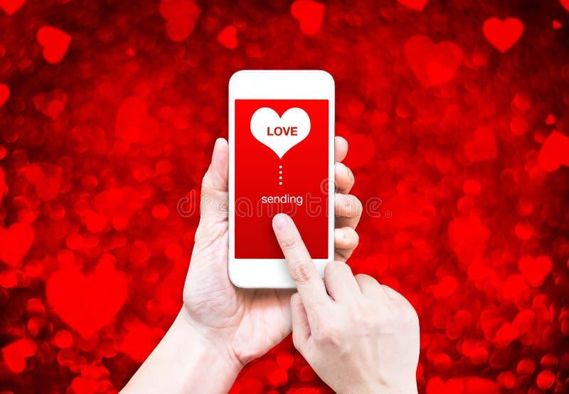Passi lo Smart Phone della tenuta con l'invio la parola di amore e della forma del cuore immagini stock