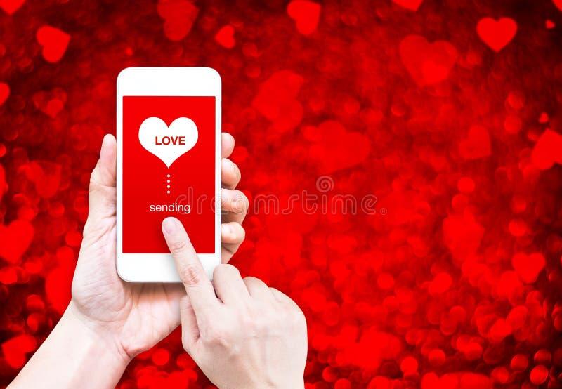 Passi lo Smart Phone della tenuta con l'invio la parola di amore e della forma del cuore immagini stock libere da diritti