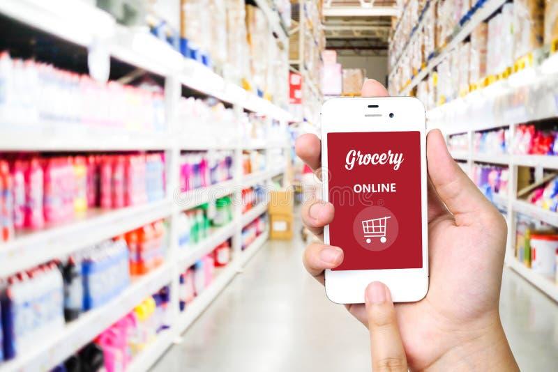Passi lo Smart Phone della tenuta con la drogheria online sullo schermo sopra sfuocatura immagini stock libere da diritti
