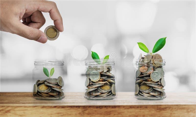 Passi mettere la moneta in bottiglie di vetro con le piante che emettono luce, i soldi di risparmio, investimento ed economizzi c fotografia stock