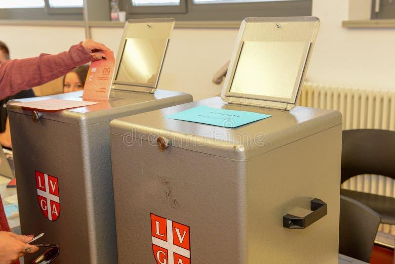Passi mettere una scheda elettorale di voto in una scanalatura della casella fotografia stock libera da diritti