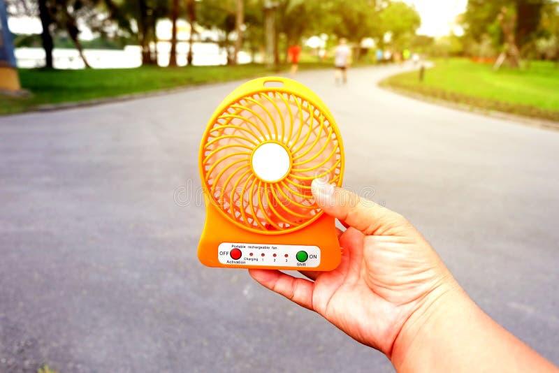 Passi a tenuta il fan portatile al parco pubblico di estate fotografia stock