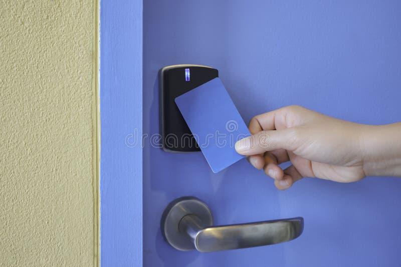 Passi a tenuta la carta chiave sulla serratura di cuscinetto di chiave del controllo di accesso immagine stock libera da diritti