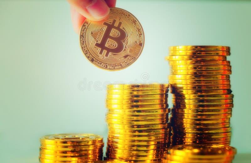 Passi a tenuta un singolo bitcoin sopra la pila di bitcoins del glod, Cryptocu fotografie stock libere da diritti