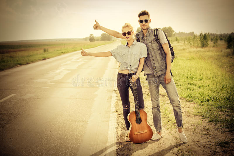 Passing car. Hitchhiking couple. Romantic young people standing on a highway and catching a passing car. Sepia, retro styled royalty free stock photo