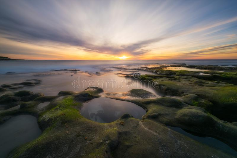 Algae covered rocks and tide pools in La Jolla California. Passing clouds at sunset over a tide pool in La Jolla California stock photos