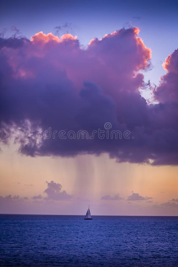 A lone sailboat in the rain. A passing storm cloud rains down on a lone boat as it sails into the Caribbean Sea stock image