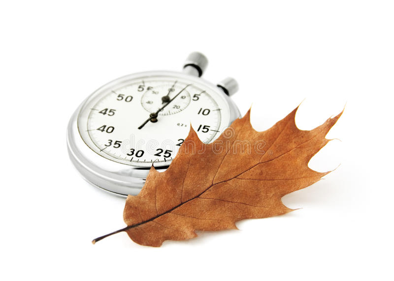 Passing time concept. Chronometer and a dry oak leaf on white. Concept of passing time, can be used for autumn sales advertisement stock photos
