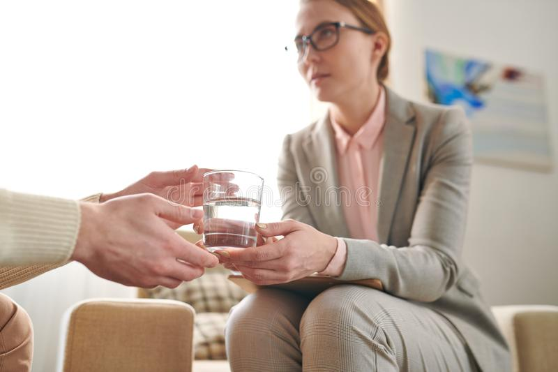 Passing water to patient. Elegant counselor passing glass of water to male patient during individual session in office royalty free stock photography