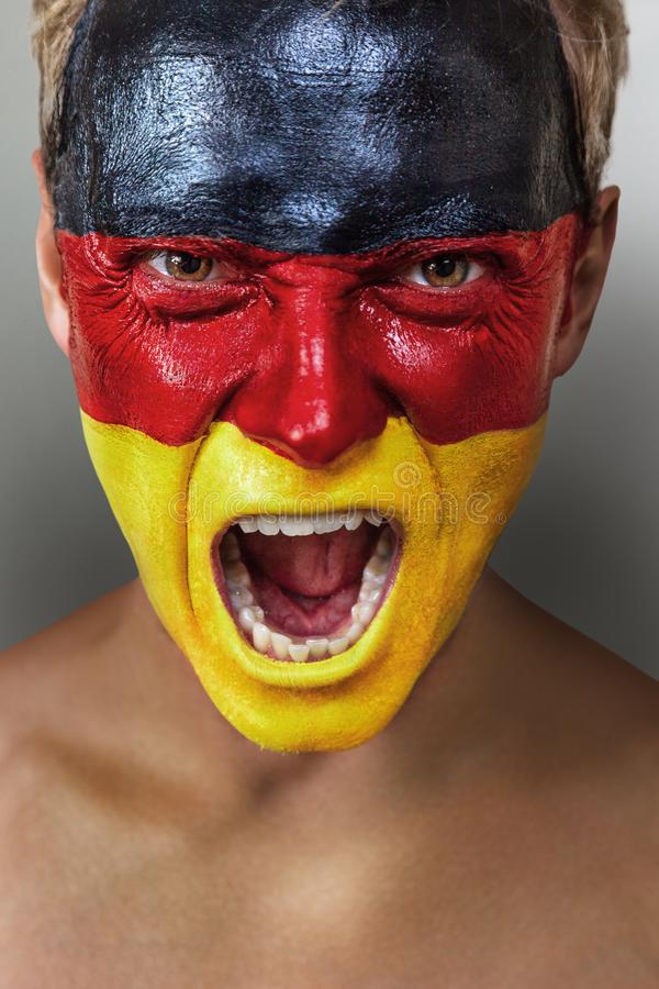 Passioné du football avec le drapeau allemand peint sur son visage photos libres de droits