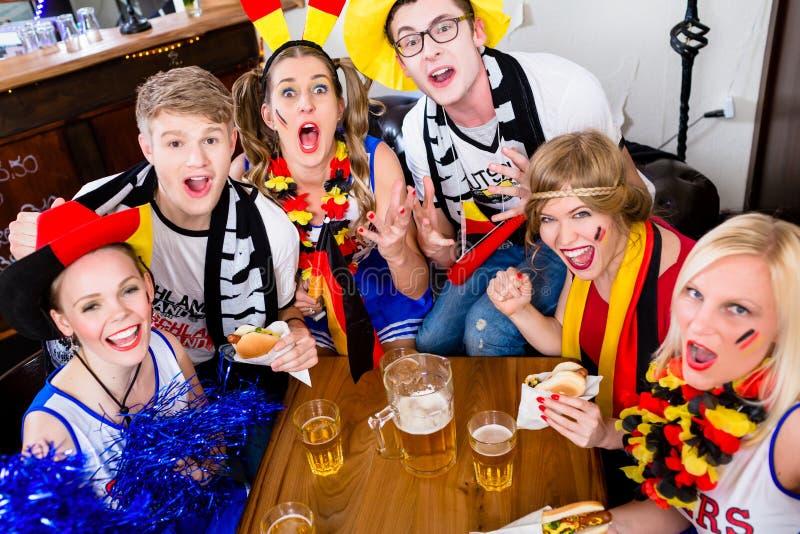 Passionés du football dans la barre de sports observant un jeu avec l'excitation photo stock