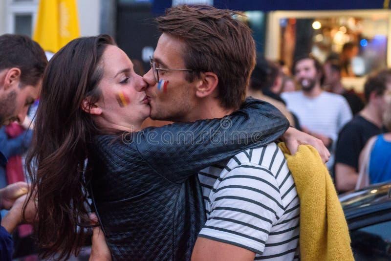 Passionés du football de la Belgique et des Frances embrassant après jeu images stock