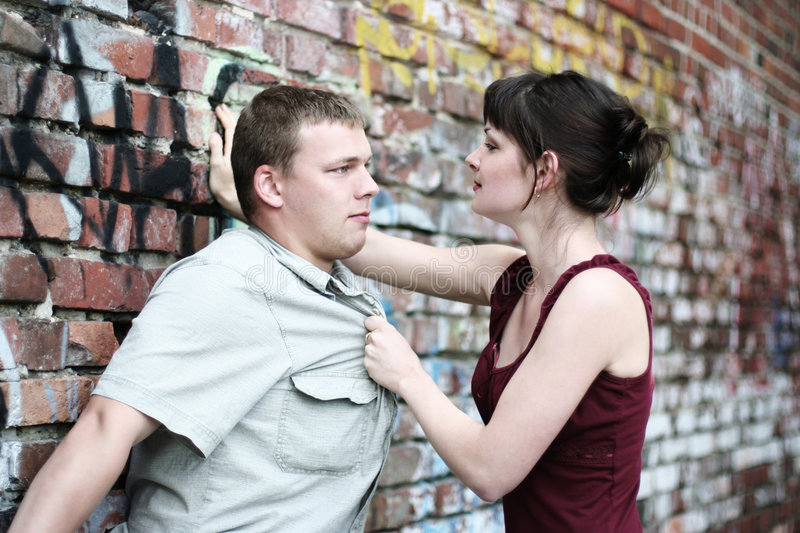 Passion. Young loving couple near the wall royalty free stock photos