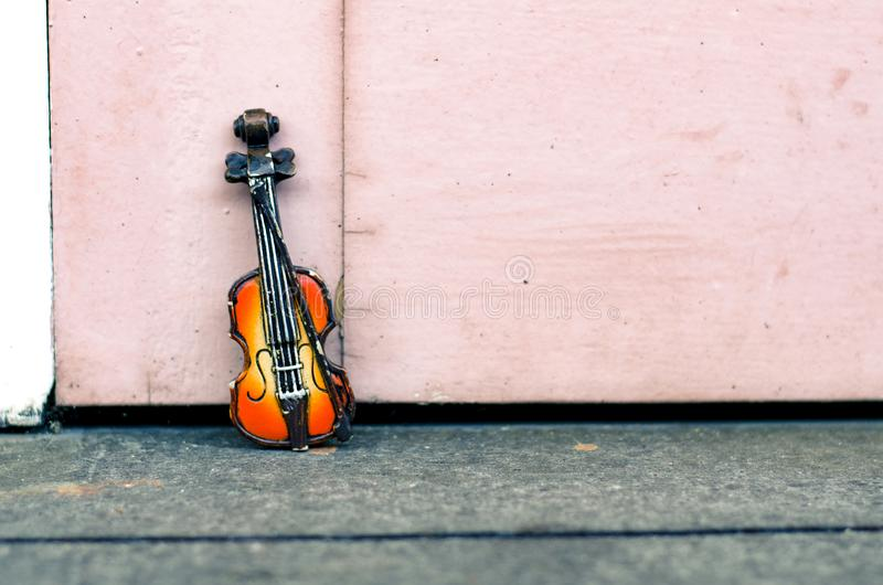 Passion de musique et concept de passe-temps, miniature de violon au-dessus de mur en bois avec le rétro ton de couleur photographie stock libre de droits