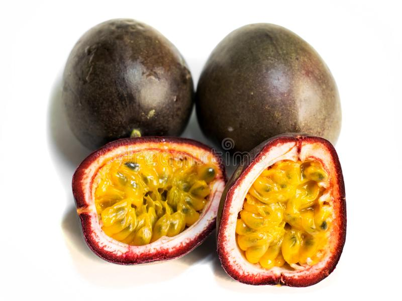 Passion fruit  Passiflora edulis.3 fruits. The fruit is cut in two halves. Isolated on a white background stock photos