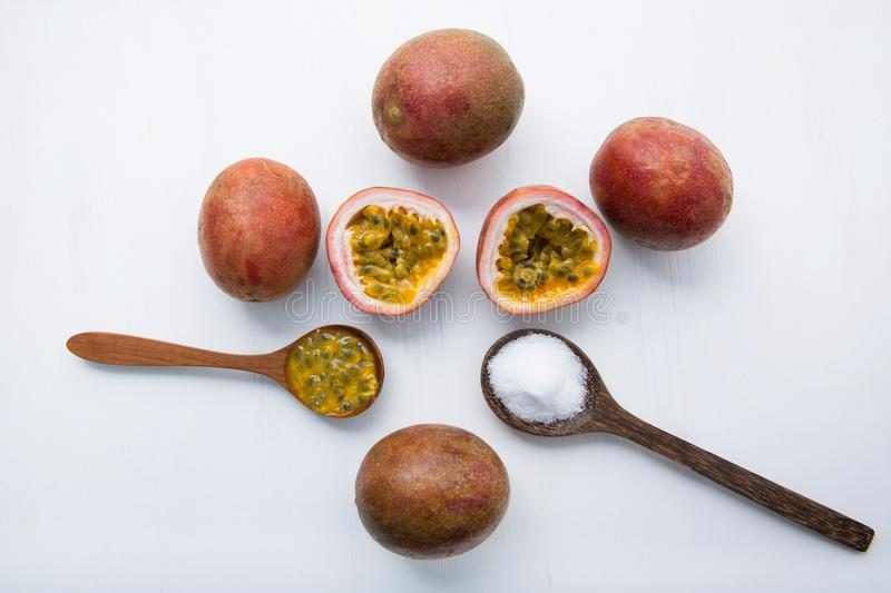 Passion fruit with salt in wooden spoon on wooden white background. stock photos