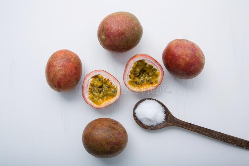 Passion fruit with salt in wooden spoon on wooden white background. royalty free stock photography