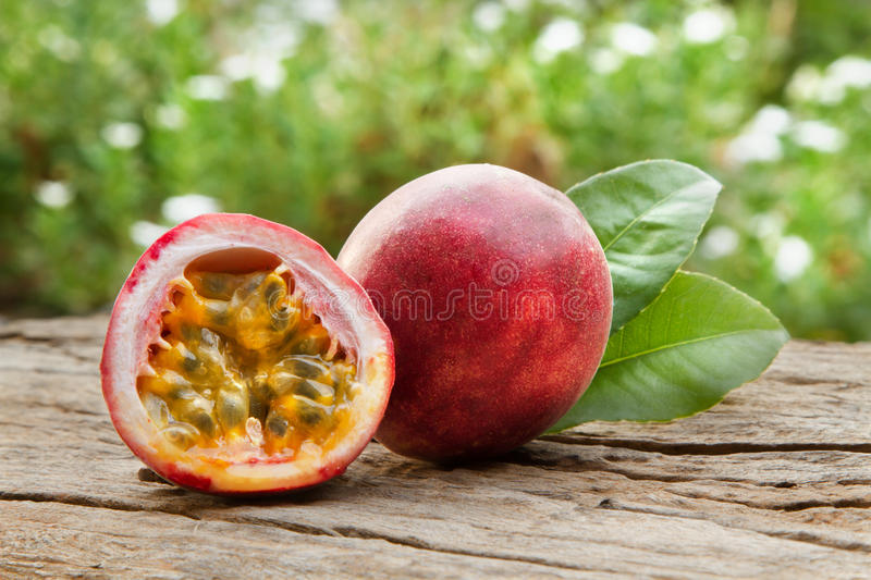 Passion fruit. On wooden table and green defocus of organic garden background royalty free stock photography