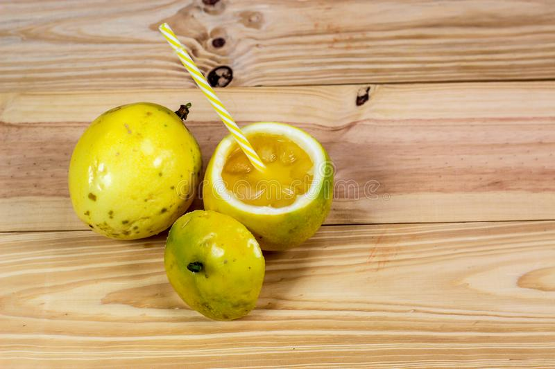 Passion fruits half and juice on the vintage wooden background stock images