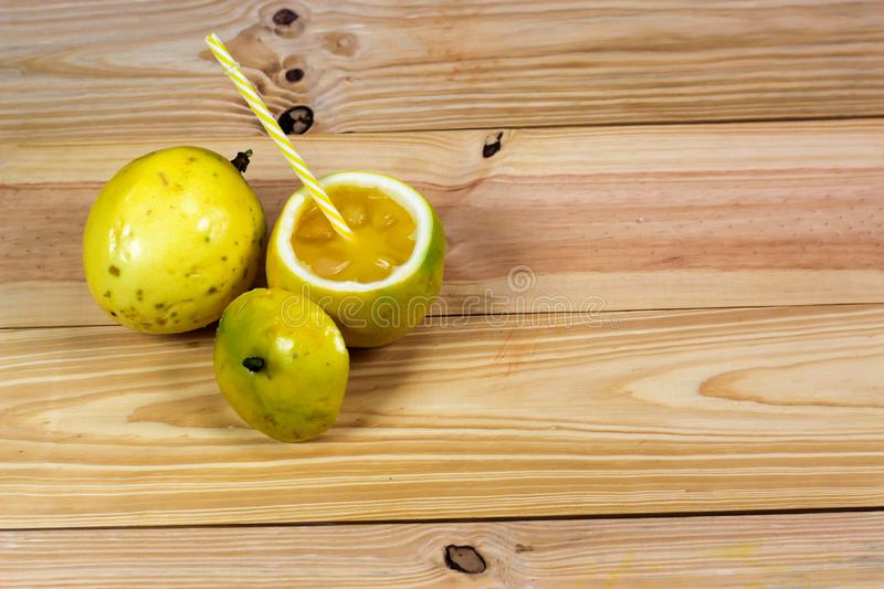 Passion fruits half and juice on the vintage wooden background stock photos