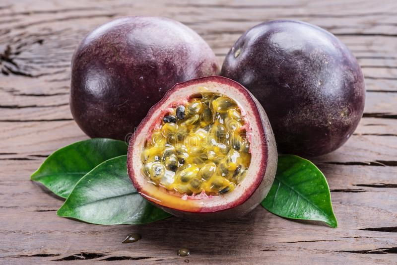 Passion fruits and its cross section with pulpy juice filled with seeds. Wooden background royalty free stock image