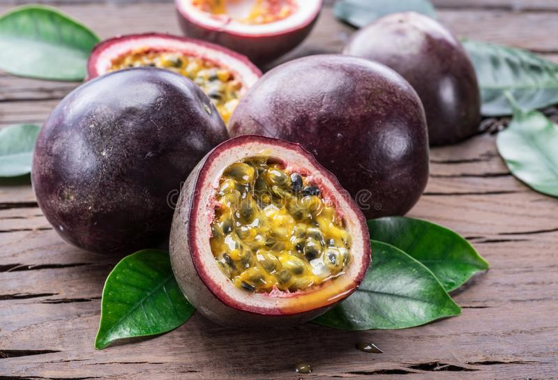 Passion fruits and its cross section with pulpy juice filled with seeds. Wooden background stock photos