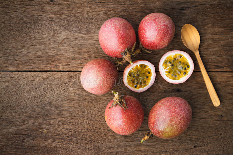 Passion fruits and slice with wooden spoon on wooden background. royalty free stock image