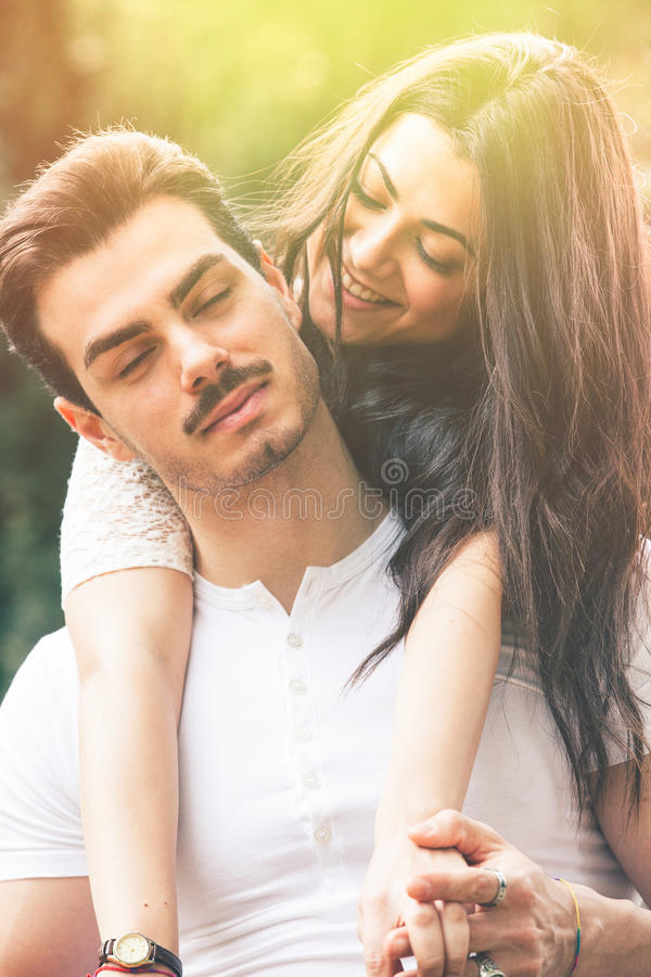 Passion and harmony. Relationship. Love and happiness. A smiling beautiful young women embracing her men from behind. Between the two there is a great harmony royalty free stock photography