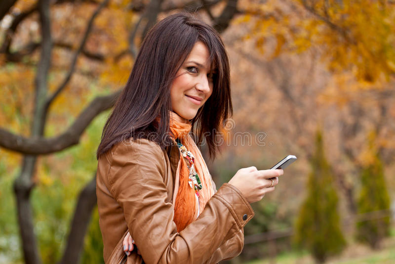 Passion for mobile technology. Beautiful young woman smiles after reading a text message on a new mobile device. Selective focus and beautiful autumn colors in