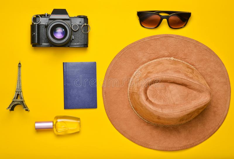 Passion for travel, wanderlust concept. Trip to France, Paris. Felt hat, film camera, sunglasses, passport, perfume bottle. Souvenir statuette of the Eiffel royalty free stock photo