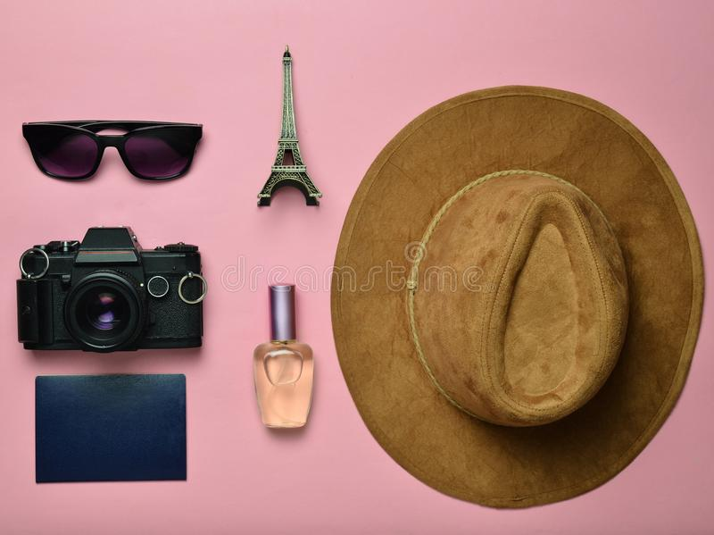 Passion for travel, wanderlust concept. Trip to France, Paris. Felt hat, film camera, sunglasses, passport, perfume bottle. Souvenir statuette of the Eiffel stock photography