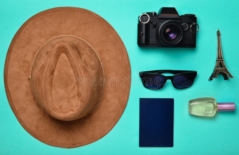 Passion for travel, wanderlust concept. Trip to France, Paris. Felt hat, film camera, sunglasses, passport, perfume bottle. Souvenir statuette of the Eiffel royalty free stock image