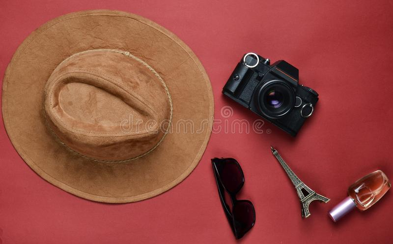Passion for travel, wanderlust concept. Trip to France, Paris. Felt hat, film camera, sunglasses, perfume bottle. Souvenir statue of Eiffel Tower layout on a royalty free stock photos