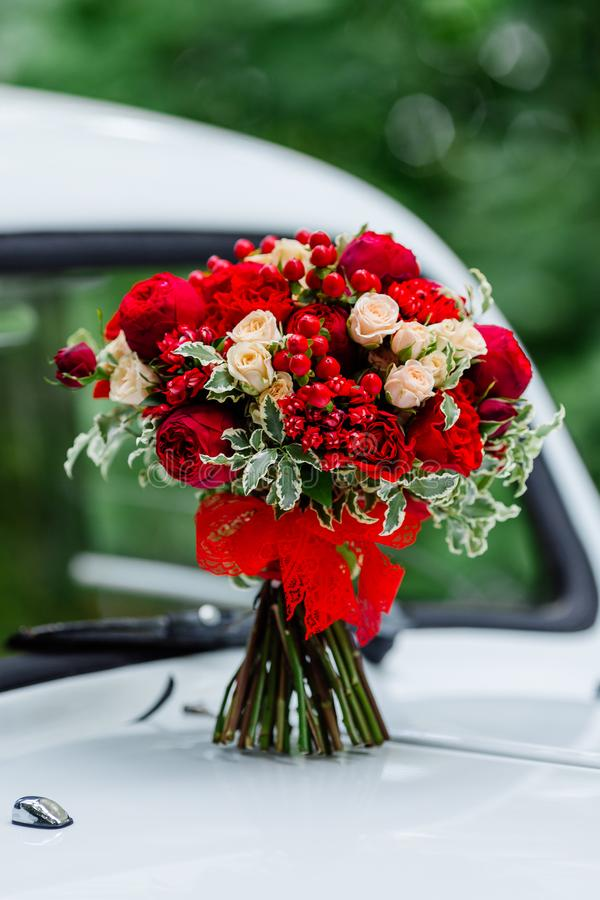 Passion wedding bouquet with dark red and marsala roses, greenery standing on white car. Bridal flowers, decorated with ribbon. Passion wedding bouquet with royalty free stock photo
