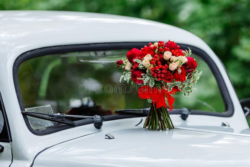 Passion wedding bouquet with dark red and marsala roses, greenery standing on white car. Bridal flowers, decorated with ribbon. Passion wedding bouquet with stock photo