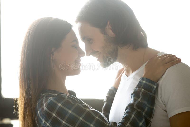 Passionate boyfriend admiring girlfriend hugging in bedroom. Passionate smiling boyfriend admire beautiful girlfriend, enjoying intimacy in bedroom, millennial stock photos