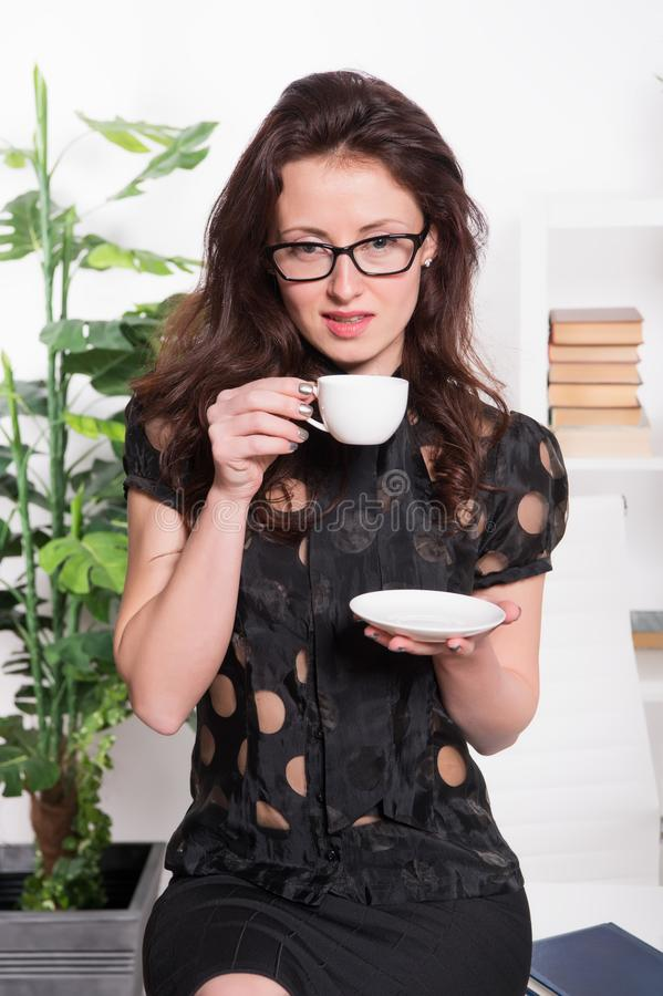 Passionate about coffee. Pretty woman drinking coffee in office. Sexy business woman with teacup sitting on desktop stock photos
