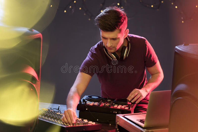 Passionate dj at turntable. Playing music at disco club royalty free stock photo